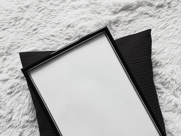 Dünner holzrahmen mit leerem exemplar als poster fotodruck mockup schwarzes kissen kissen und flauschige ...
