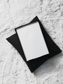 Dünner holzrahmen mit leerem exemplar als poster-fotodruck-modell, schwarzes kissenkissen und flauschige weiße decke, flacher hintergrund und kunstprodukt-draufsicht