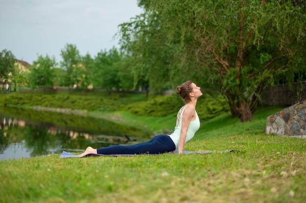 Dünner junger brunettejogi führt yogaübungen auf dem grünen gras durch