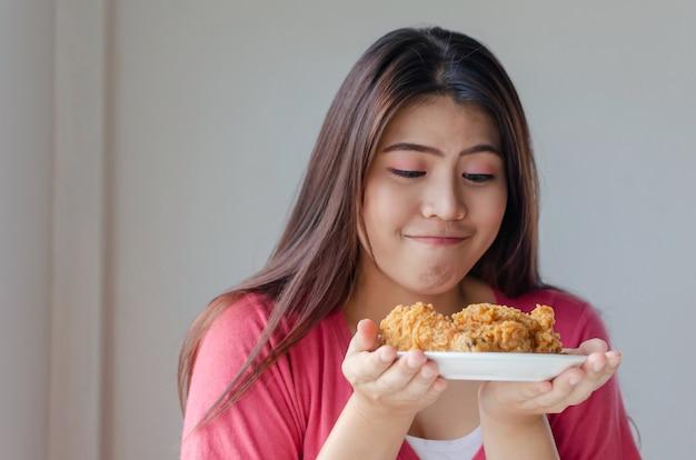 Dünner körper der asiatischen jungen hübschen frau, der köstliches knusperiges gebratenes huhn auf teller im büro der küche zu hause genießt und hält