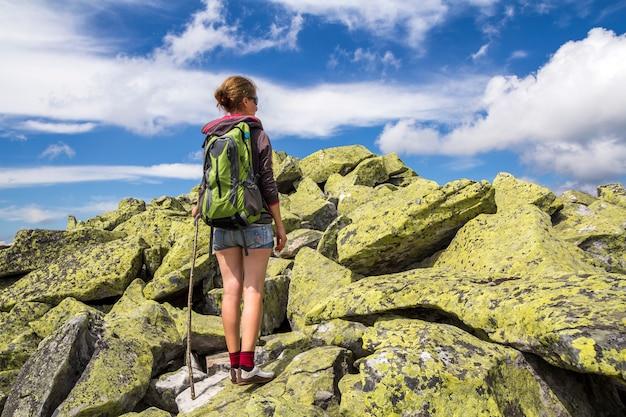 Dünnes athletisches blondes touristisches wanderermädchen mit dem stock- und rucksackklettern beleuchtete durch hohen felsigen berg der sonne auf hellem blauem himmel. tourismus, reisen, wandern und gesundes lebensstilkonzept.