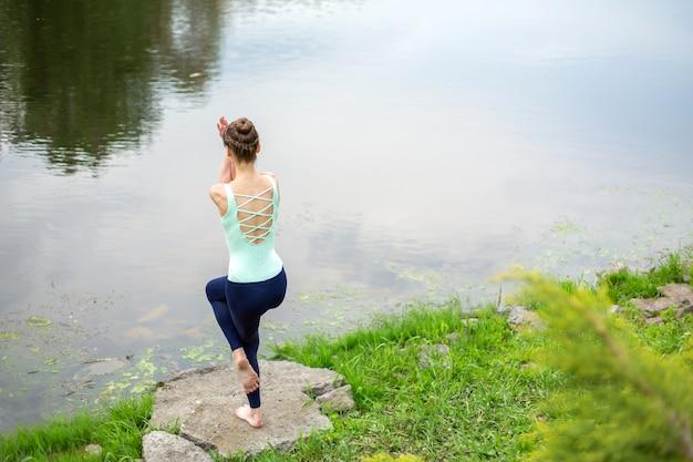 Dünnes brunettemädchen, das yoga im sommer auf einem grünen rasen durch den see tut