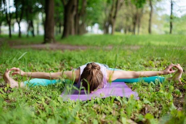 Dünnes brunettemädchen spielt sport und führt die schönen und hoch entwickelten yogahaltungen in einem sommerpark durch. grüner üppiger wald auf. frau, die übungen auf einer yogamatte tut