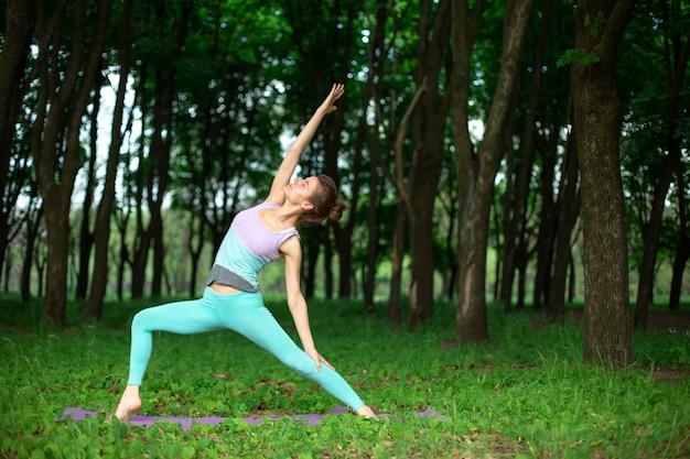 Dünnes brunettemädchen spielt sport und führt die schönen und hoch entwickelten yogahaltungen in einem sommerpark durch. grüner üppiger wald. frau, die übungen auf einer yogamatte tut