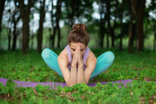 Dünnes brunettemädchen spielt sport und führt die schönen und hoch entwickelten yogahaltungen in einem sommerpark durch. grüner wald auf der. frau, die übungen auf der yogamatte tut. lotus-pose