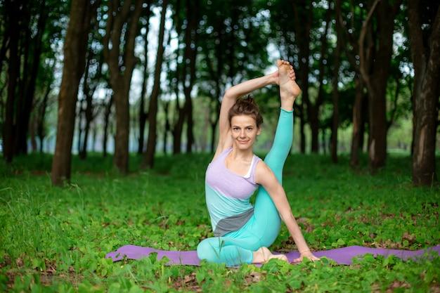 Dünnes brunettemädchen spielt sport und führt die schönen und hoch entwickelten yogahaltungen in einem sommerpark durch