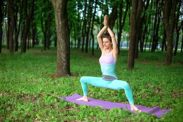 Dünnes brunettemädchen spielt sport und führt die schönen und hoch entwickelten yogahaltungen in einem sommerpark durch.