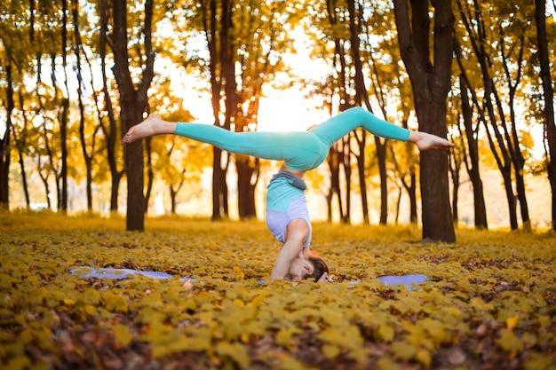 Dünnes brunettemädchen spielt sport und führt yogahaltungen im herbstpark auf einem sonnenuntergang durch. frau, die übungen auf der yogamatte tut. herbstlicher wald. weicher fokus
