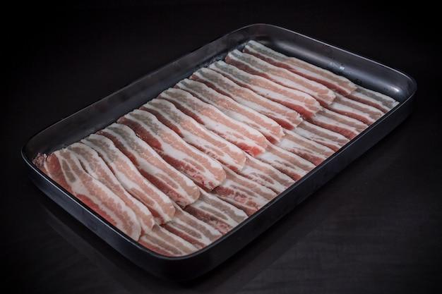 Dünnes geschnittenes schweinefleisch, sukiyaki, shabu shabu-menü, japanisches lebensmittelmenü auf schwarzem hintergrund
