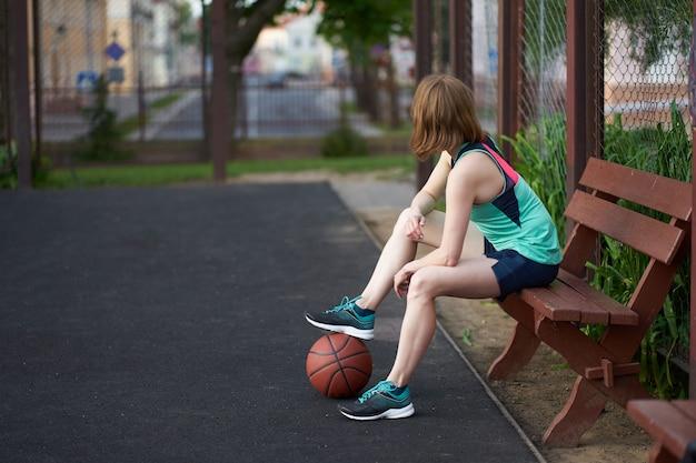 Dünnes kaukasisches mädchen der rothaarigen mit ball aus den grund, der auf ein spiel auf basketballplatz im freien sitzt und wartet