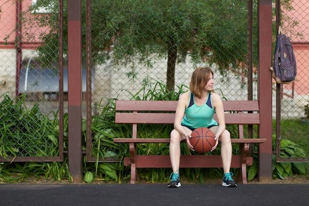 Dünnes kaukasisches mädchen der rothaarigen mit ball in ihren händen, die auf ein spiel auf basketballplatz im freien sitzen und warten