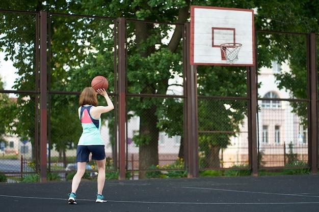 Dünnes mädchen der rothaarigen, das draußen einen ball in basketballkorb wirft