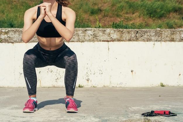 Dünnes mädchen in der sportkleidung, die draußen morgens sit-ups tut