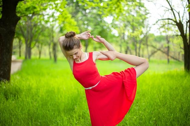 Dünnes schönes brunettemädchen in einem roten kleid führt yogahaltungen in einem sommerpark durch. grüner wald bei sonnenuntergang