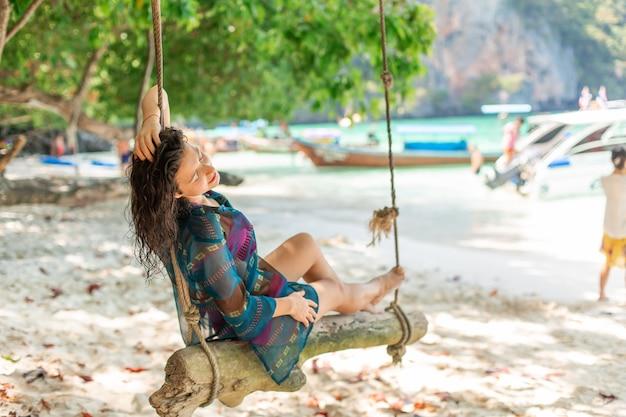 Dünnes sexy mädchenmodell in einem badeanzug, der auf einem hölzernen schwingen gebunden an einem baum aufwirft. auf dem strand einer tropischen insel.