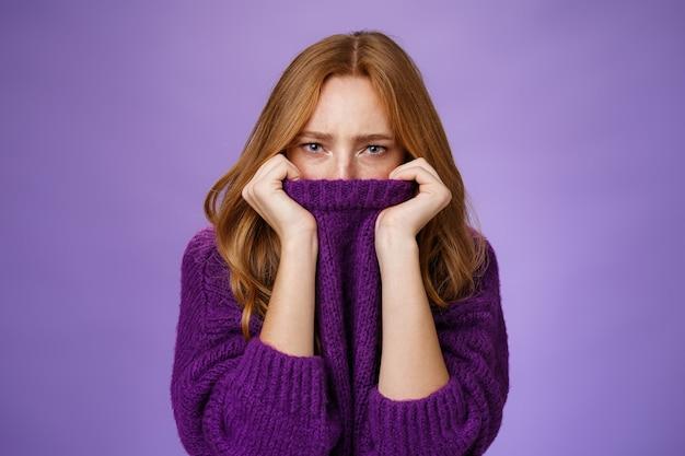 Düster verärgerte rothaarige freundin, die den kragen des lila pullovers auf der nase zieht, die stirn runzelt und die augen zusammenkneift, beleidigt und ärgerlich ist, schmollend launisch und unzufrieden über violettem hintergrund.
