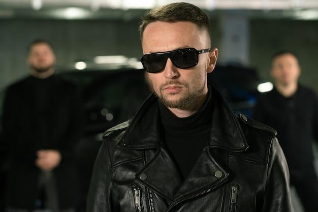 Düstere kriminelle autorität in sonnenbrille und schwarzer lederjacke, die auf parkplatz mit seiner bande auf hintergrund stehen