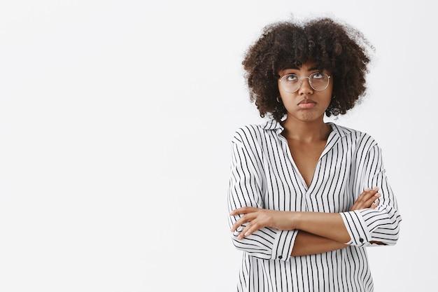 Düstere und verärgerte, gut aussehende afroamerikanerin, die sich düster fühlt und pläne für die nacht bereut, ruiniert die lippen, die nach oben schauen und vor enttäuschung die hände auf der brust kreuzen