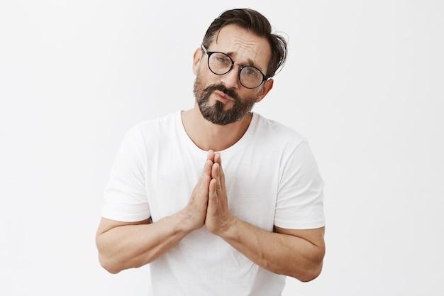 Düsterer bärtiger reifer mann mit brille, die aufwirft