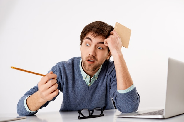 Düsterer junger gelangweilter kerl bei der arbeit, der bleistift als abstand während des brainstormings betrachtet, ideen ausdenkt, inspiration fehlt, in der nähe des laptops sitzt, planer hält