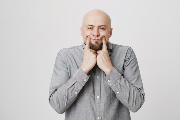 Düsterer kerl zieht lächeln mit den fingern