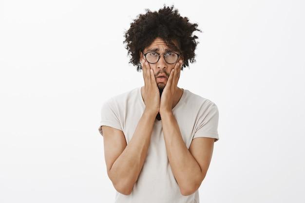 Düsterer und verzweifelter junger männlicher programmierer, der enttäuscht aussieht