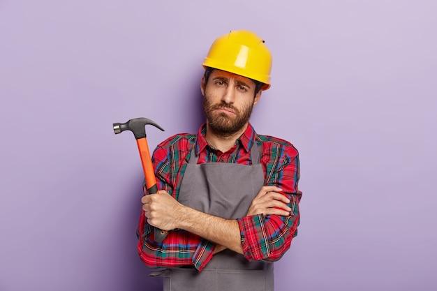 Düsterer unglücklicher männlicher reparaturbetrieb hat einen traurigen, müden blick, drückt die hände, hält den hammer in der hand, müdigkeit nach der reparatur und manuelle arbeit, trägt eine spezielle uniform. handarbeit, hämmern, bauen.