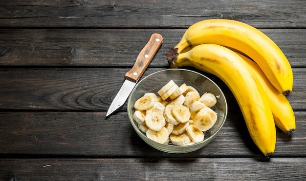 Duftende bananen und bananenscheiben in einer glasschüssel mit einem messer. auf einem schwarzen hölzernen hintergrund.