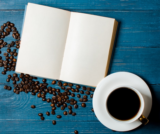 Duftende geröstete kaffeebohnen, ein buch und eine tasse kaffee auf whi