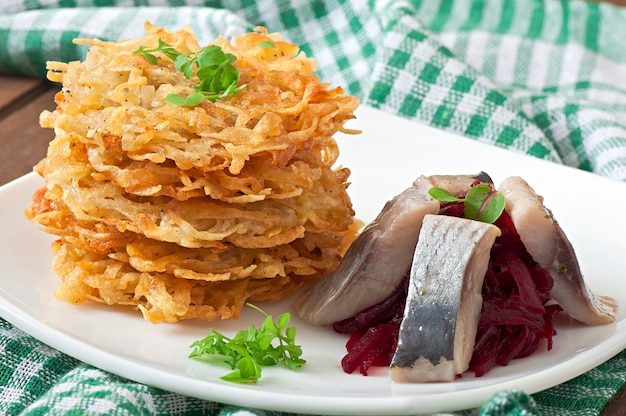 Duftende kartoffelpuffer und hering mit rote beete