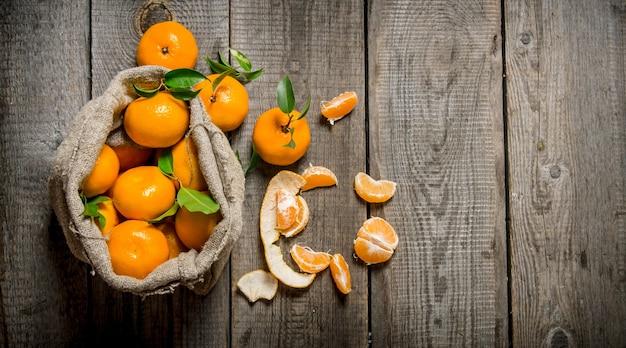 Duftende mandarinen in einer alten tüte mit einem messer und geschälten mandarinen. auf hölzernem hintergrund. freier platz für text. draufsicht