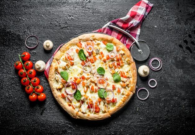 Duftende pizza mit hühnchen und tomaten.