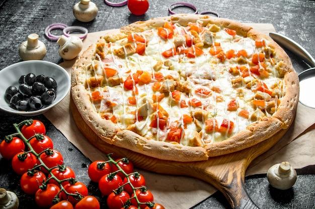 Duftende pizza mit huhn und tomaten auf dunklem holztisch