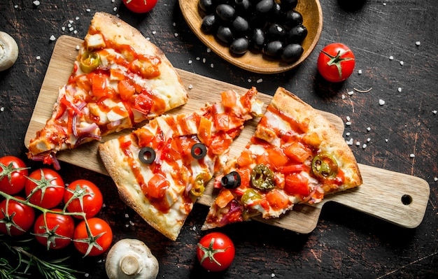 Duftende pizza mit oliven, tomaten und pilzen auf dunklem rustikalem tisch.
