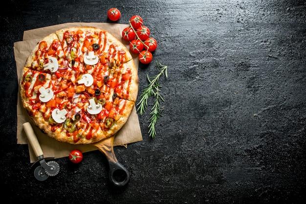 Duftende pizza mit tomaten und rosmarin. auf schwarzem rustikalem hintergrund