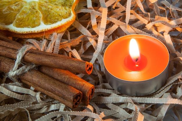 Duftende stöcke zimt und orangenscheibe mit einer brennenden roten kerze, das konzept eines gemütlichen abends