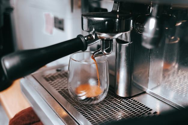 Duftender espresso fließt aus einer kaffeemaschine in eine tasse.