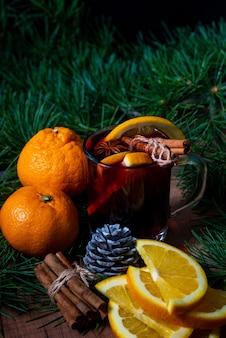 Duftender glühwein, gewürze und mandarinen am weihnachtsbaum