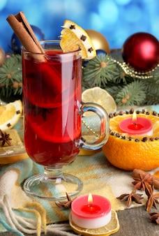 Duftender glühwein im glas mit gewürzen und orangen auf holztisch auf blau