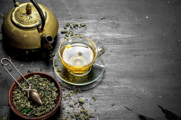 Duftender grüner tee mit blättern an der schwarzen tafel