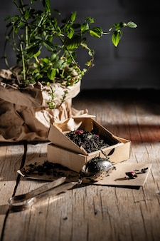 Duftender tee mit früchten und blumen in kraftverpackung auf dem tisch, dekoriert mit einem topf minze