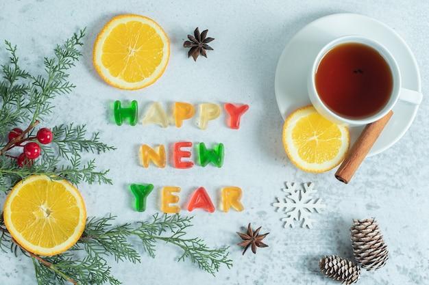 Duftender tee mit gelee und orangenscheiben auf weiß.