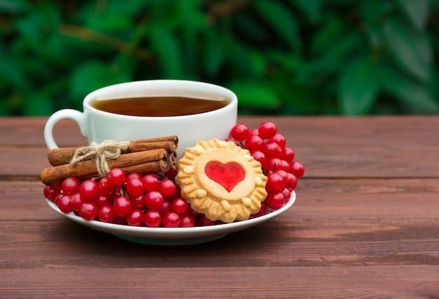 Duftender tee mit zimt, preiselbeeren und keksen