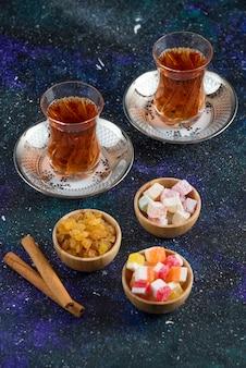 Duftender tee und köstlichkeiten auf blauer oberfläche
