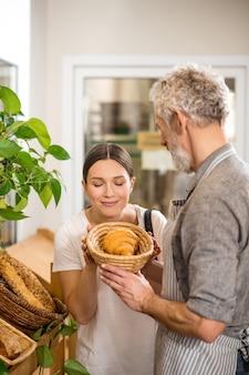 Duftendes croissant. dunkelhaarige hübsche frau mit geschlossenen augen, die das aroma von croissant aus dem korb in den händen des grauhaarigen verkäufers einatmet