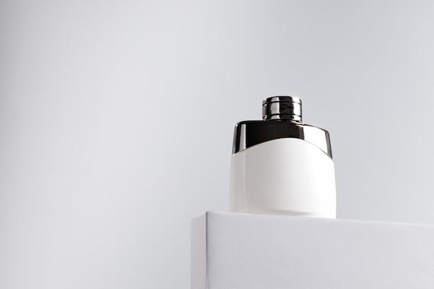 Duftflasche auf grauem block gegen grauen hintergrund schließen