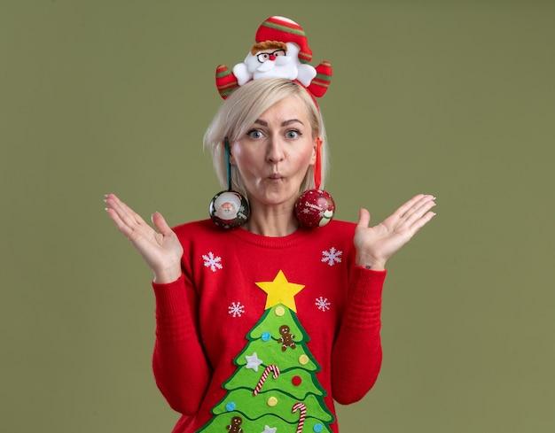 Dumme blonde frau mittleren alters mit weihnachtsmann-stirnband und weihnachtspullover, die mit geschürzten lippen aussieht und leere hände mit weihnachtskugeln zeigt, die von ihren ohren hängen, isoliert auf olivgrüner wand