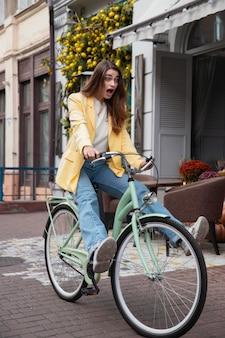 Dumme frau, die ihr fahrrad draußen in der stadt reitet