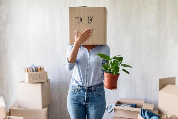 Dumme frau, die mit kasten über kopf und pflanze in der hand beim packen aufwirft, um sich zu bewegen