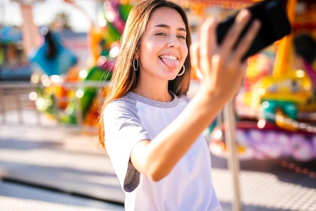 Dumme frau, die selfie mit telefon nimmt